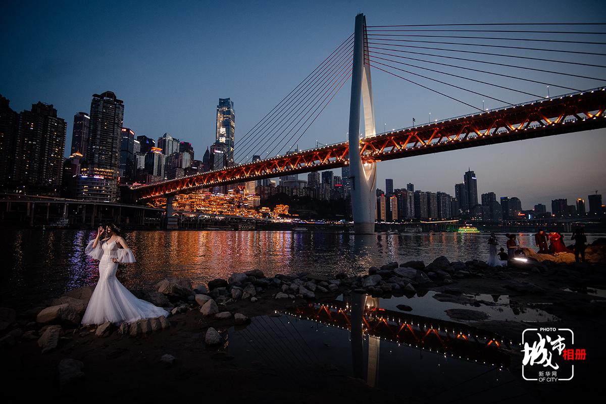 漲水前,千廝門大橋下的江邊是不少人愛來的拍照地。江水靜靜流淌,這一座現代化的都市被襯托得靜謐而美好。夜幕初臨,一女子正在拍攝婚紗照,鏡頭按下的一剎那,定格住人的美麗瞬間,也記錄下這一方天地間的水天相接、錯落高樓、夜色霓光。新華網 李相博 攝