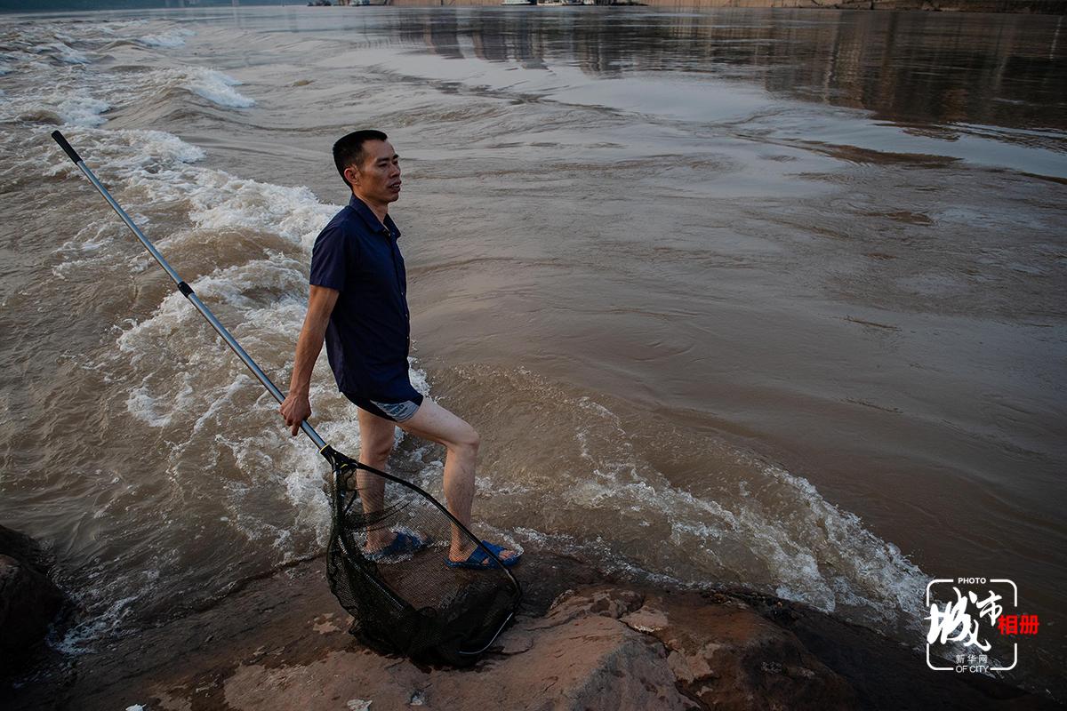 """""""漲水魚,落水蝦"""",以往江水上漲時,江邊擠滿了漁民。如今,在岸邊撒網撈魚不再是為了生計。拿著漁網離去時雖兩手空空,但捕魚者臉上卻喜悅不減,漲水撈魚更像是一種對老時光的重溫。新華網 李相博 攝"""