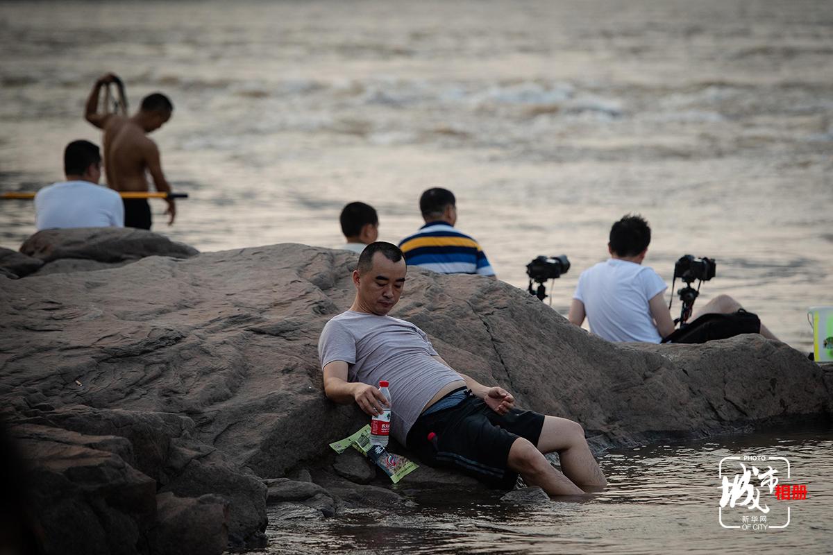 炎炎夏日,還有什麼比江中泡水更消暑?江上礁石成了座椅,閒倚石上,將腳泡進沁人的江水中,以水代酒,一口花生一口酒,看著落日西沉,水起水落,偷得浮生半日閒的時光在此刻顯得悠然而愜意。新華網 李相博 攝